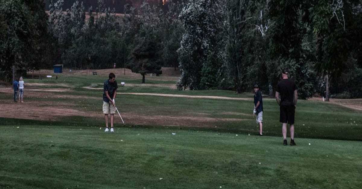 Incredible photos show golfers playing as wildfire rages behind them