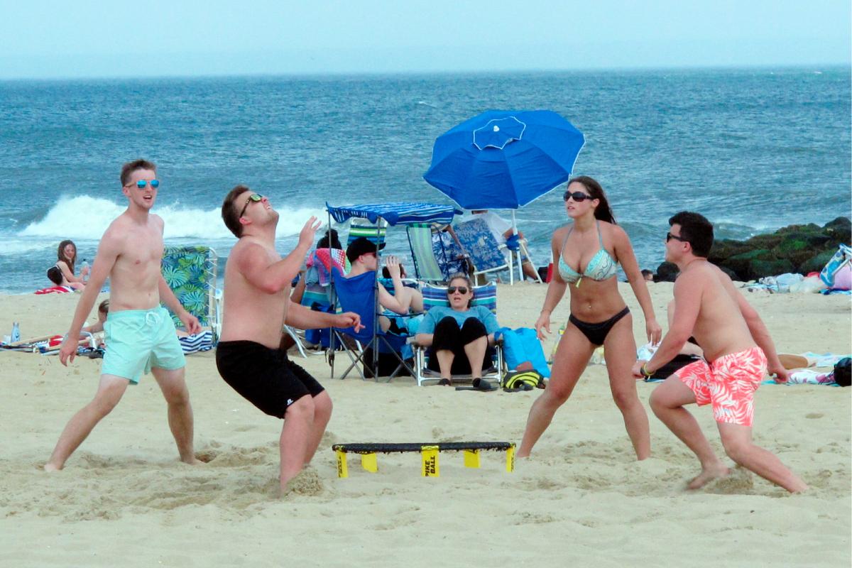 Friends play Spikeball on the beach.